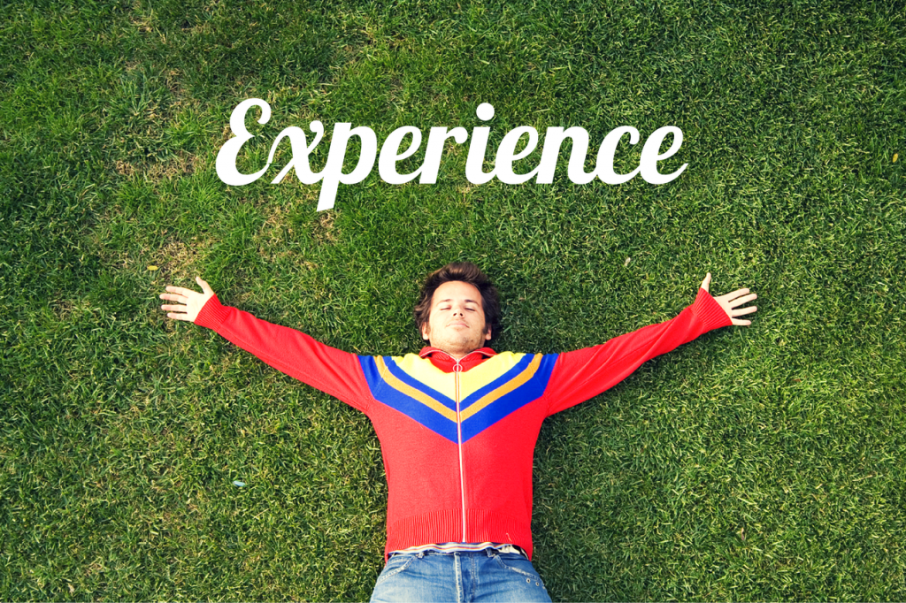 "Man lying happily on the grass and the word ""Experience"""