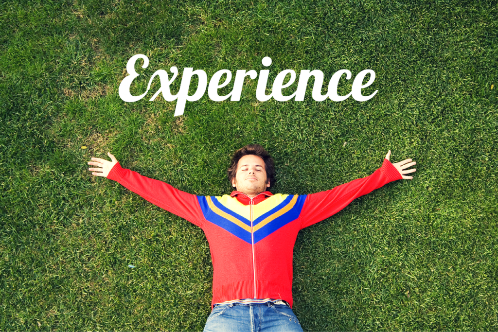 """Man lying happily on the grass and the word """"Experience"""""""