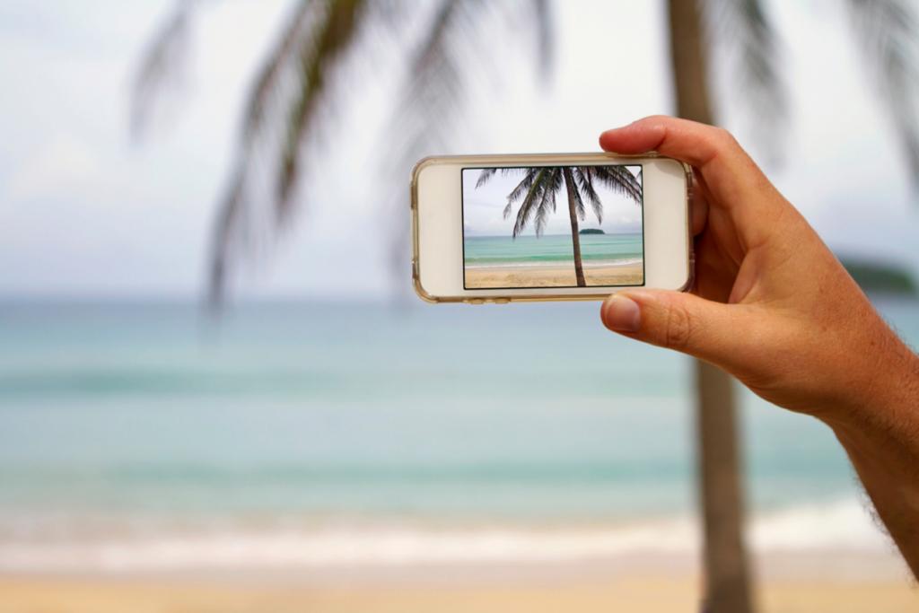 Smart phone taking photo of a beach