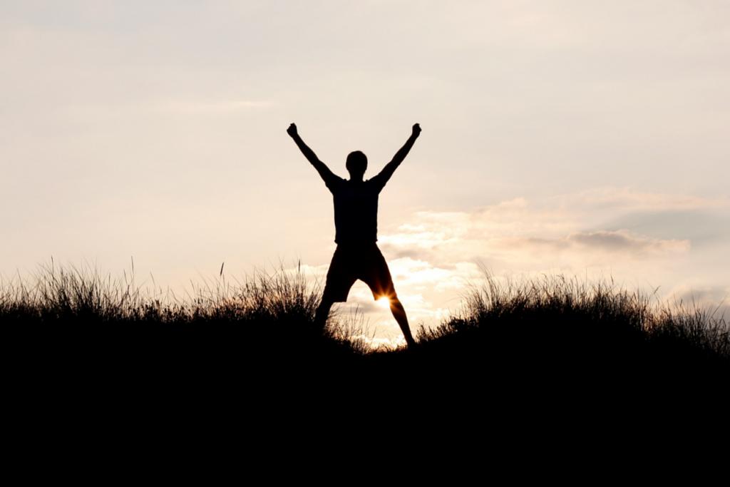 Man raising his arms in triumph at dusk