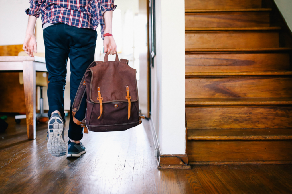 Young fashionable man carrying bag