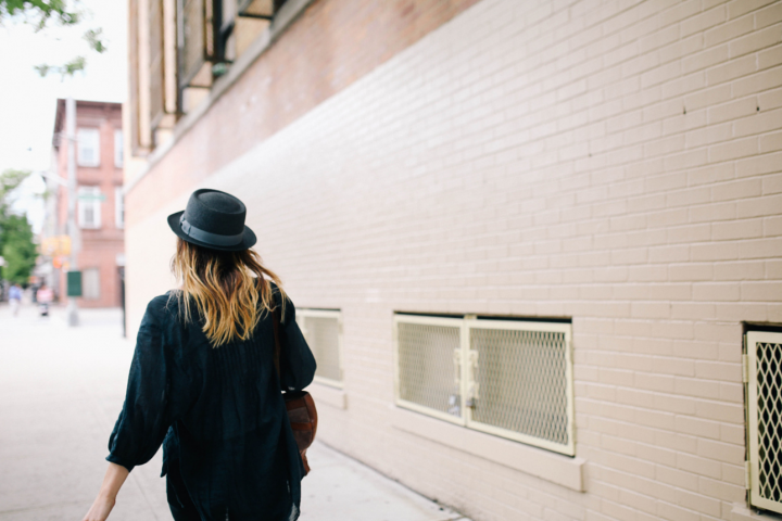 Girl in black hat walking through the street