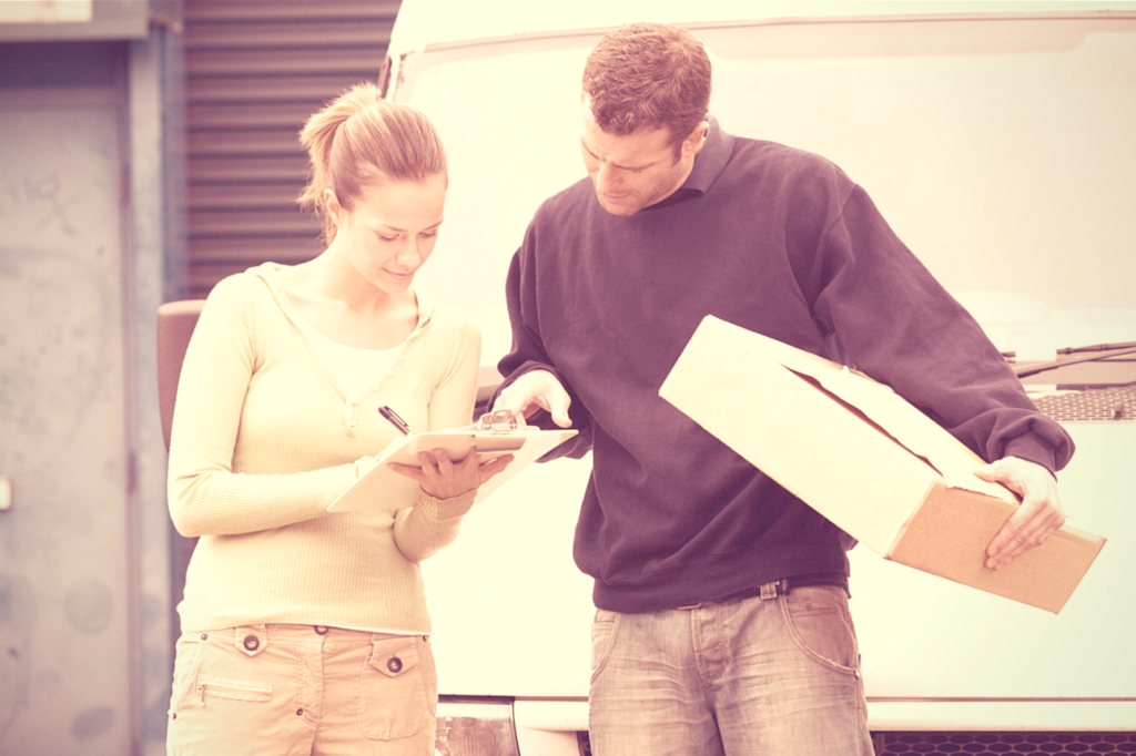 Man watching as woman signs for parcel delivery