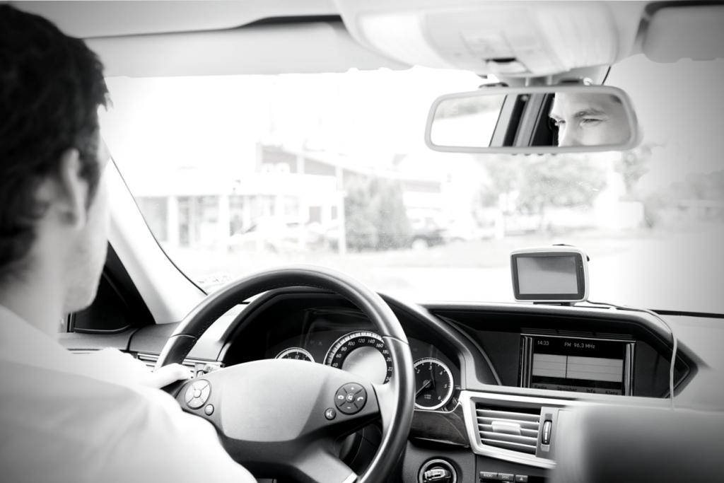 Photo of man driving car taken from back seat