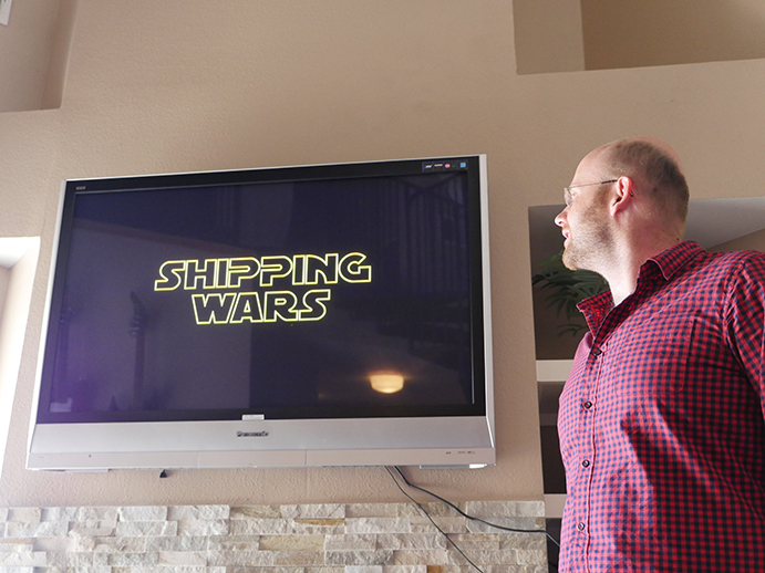 Jason standing in front of a screen that says shipping wars