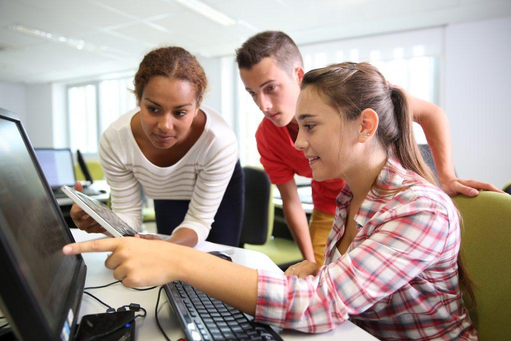 interns working together at a computer during summer internship