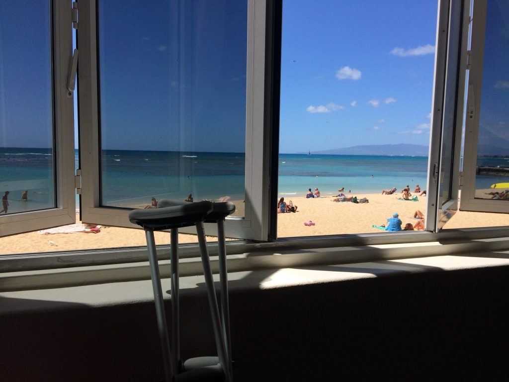 crutches leaning against the window with beach outside