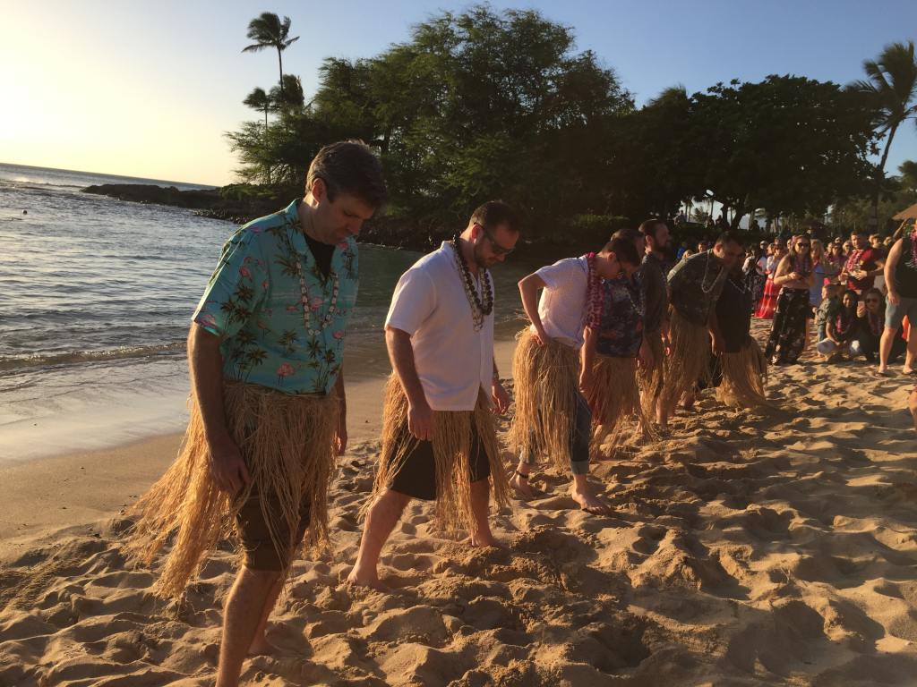 Men in grass skirts preparing to dance