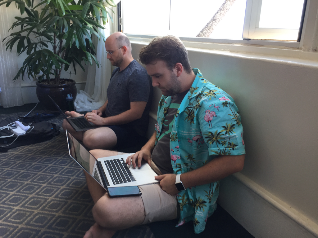 Two people sitting down cross legged with laptops at Prosparadise