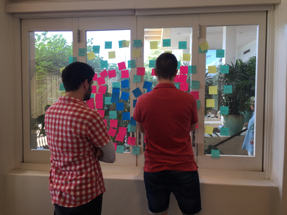 Two men looking at a display board of postit notes
